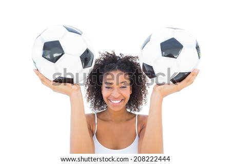 Pretty girl holding footballs and smiling at camera on white background