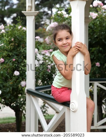 Pretty girl hugging a gazebo pole, with flower bushes in background