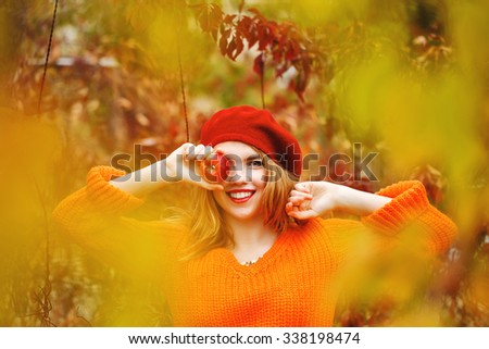 Pretty girl in a beret and a sweater in autumn park, holding a ripe apple and smiling. Girl hiding eye for fruit. The girl white smile. The concept of healthy teeth.