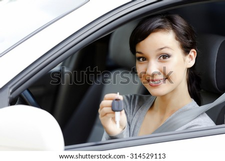 Pretty girl in a car showing the key