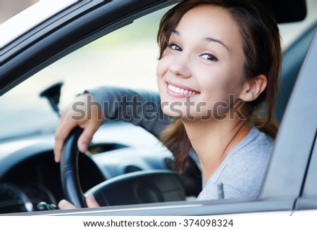 Pretty girl in a car smiling to you - stock photo