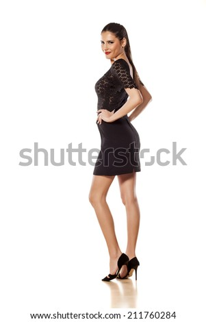 pretty girl in a dress standing on white background - stock photo