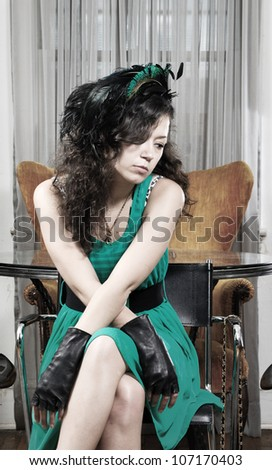 pretty girl in a green dress sitting in a home living room