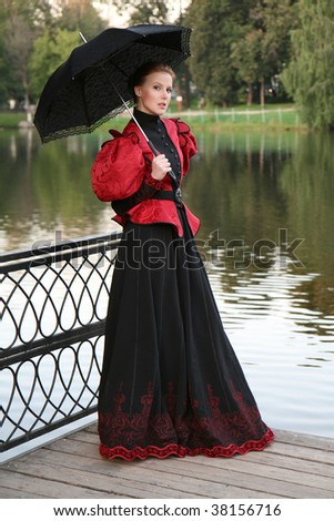 Pretty girl in a historical dress with an umbrella