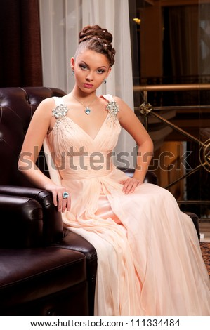 pretty girl in a long dress sitting on a leather couch - stock photo