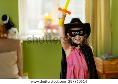 Pretty girl in a superhero suit raises her sword up - stock photo