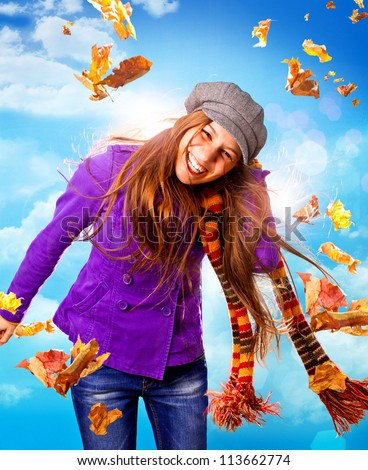 pretty girl in autumn wind with leaves - stock photo