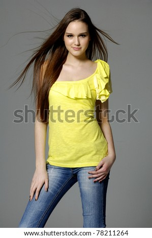 Pretty girl in blue jeans with long hair on gray - stock photo