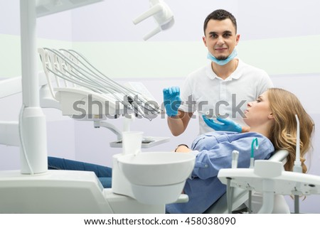 Pretty girl in blue shirt and jeans on the patient chair. Next to her there is a dentist in a white uniform with blue latex gloves and a blue mask. He holds an implant in the right hand and teeth - stock photo