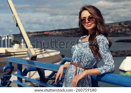 Pretty girl in blue summer dress against sea - stock photo