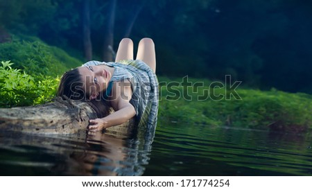 Pretty girl in cotton dress is laying on the log. - stock photo