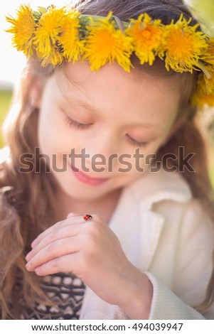 Pretty girl in dandelion wreath adores ladybug on her hand