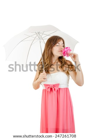 Pretty girl in elegant pink dress standing under umbrella smelling rose in sensual retro style