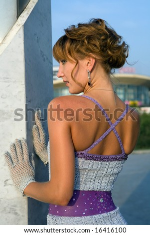 Pretty girl in exclusive woolen dress near the marble wall.