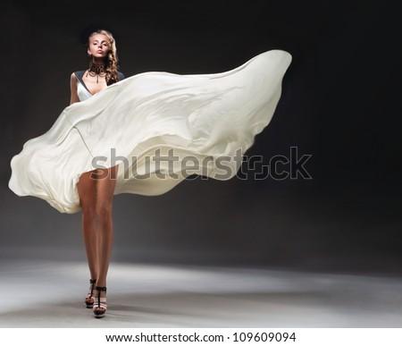 Pretty girl in fluttering dress - stock photo