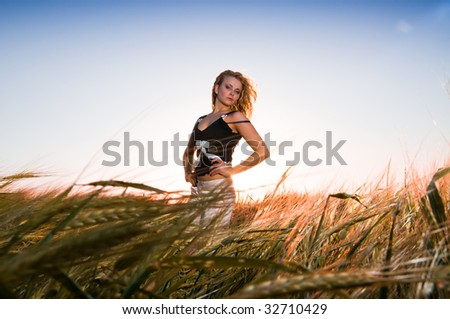 Pretty girl in golden wheat - stock photo