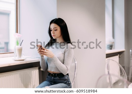 Pretty girl in grey shirt reads something in her phone sitting in the cafe
