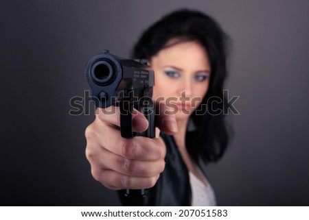 pretty girl in leather jacket with gun in hands on a gray background