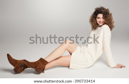 pretty girl in long white sweater and brown leather boots - stock photo