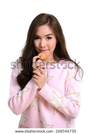 Pretty girl in pink sweater has a little smile while holding cookie in her hand on white background.