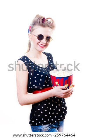Pretty girl in polka dot dress with sun glasses and popcorn looking at camera isolated on white background - stock photo