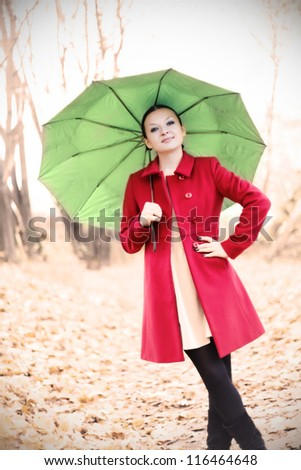 pretty girl in red coat with umbrella in autumn - stock photo