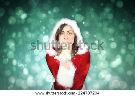 Pretty girl in santa outfit blowing against blue abstract light spot design