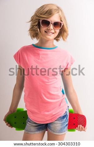 Pretty girl in sunglasses holding skateboard behind her back against white background. - stock photo