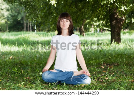Pretty girl in sunny summer park sits in a yoga pose