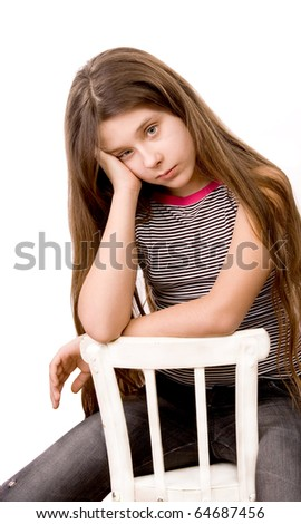 Pretty girl in the age of eleven sitting on a chair isolated on white - stock photo
