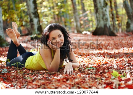 Pretty girl in the autumn forest laying on yellow leaves - stock photo