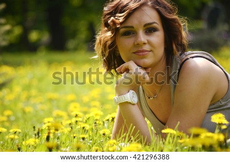 pretty girl in the grass with dandelions