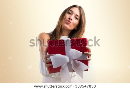 Pretty girl in white dress holding a gift - stock photo