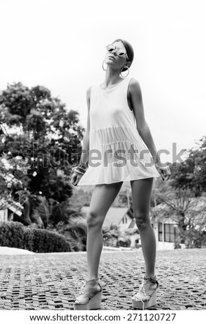 Pretty girl in white short dress walking down the street on a sunny day. Outdoors lifestyle black and white portrait