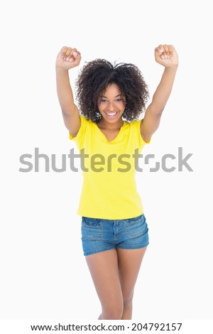 Pretty girl in yellow tshirt and denim hot pants cheering at camera on white background