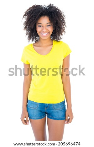 Pretty girl in yellow tshirt and denim hot pants smiling at camera on white background - stock photo