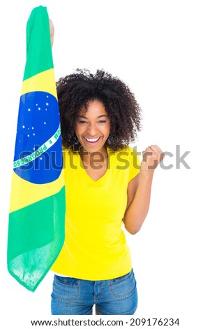 Pretty girl in yellow tshirt holding brazilian flag cheering at camera on white background