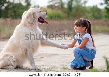 Pretty girl is playing with dog in the nature. She is kneeling and smiling. The animal is giving her fin with joy - stock photo