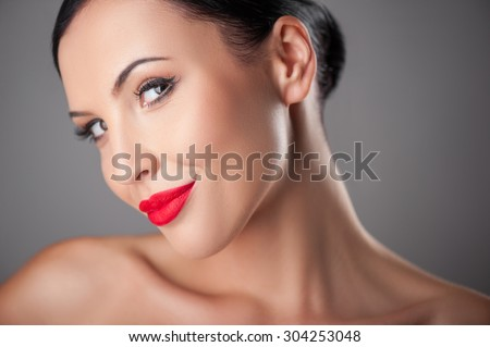 Pretty girl is posing and seducing. She is looking at the camera flirtingly and smiling. She has naked shoulders and red lips. Isolated on background - stock photo