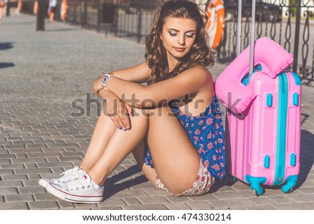 Pretty girl is sitting near suitcase