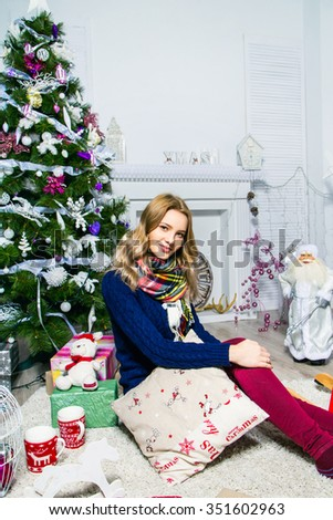 Pretty girl is sitting near the Christmas tree and fireplace with a gift in the white room. Christmas and New Year concept