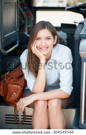 Pretty girl is sitting on the steps of the bus and waiting for its moving. She is looking at the camera and smiling. The lady is leaning her head on her hand - stock photo