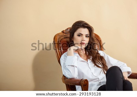 Pretty girl is situated on furniture and looking seriously at the camera. Her hand is propping up her head. She is boss. Isolated on brown background and there is copy space in the left side - stock photo