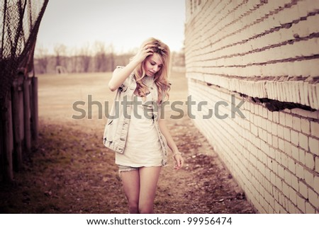 Pretty girl is walking in the city - stock photo