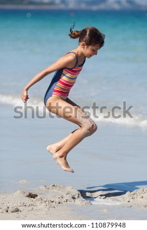 pretty girl jumps at the beach to hit a puddle - stock photo