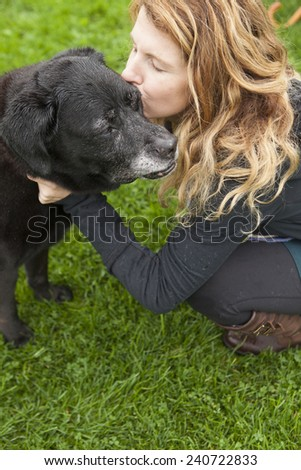 Pretty girl kissing her aging and  senior dog