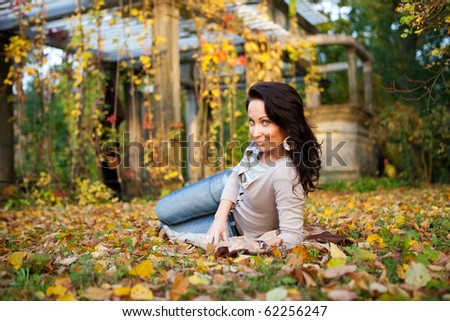 Pretty girl laying on leafs in the autumn park - stock photo