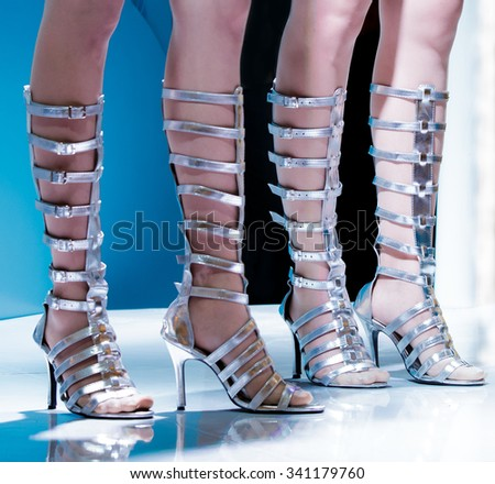 Pretty girl leg on stage with boots fashion shoes. - stock photo