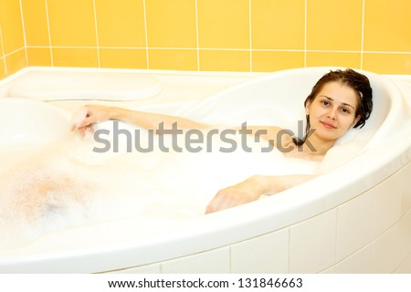 Pretty girl lies naked in a bathtub with foam