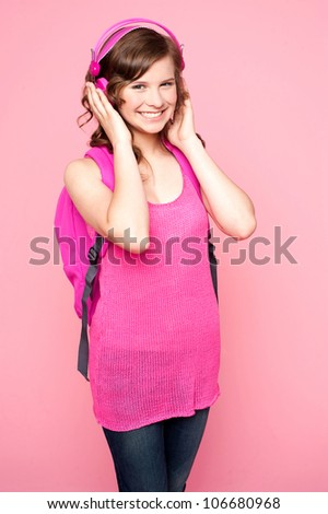 Pretty girl listening to music through headphones and carrying school bag - stock photo